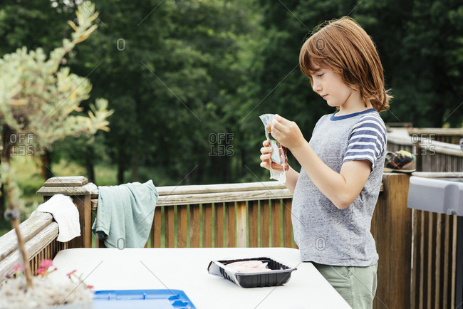 Boy holding package of hot dogs at picnic