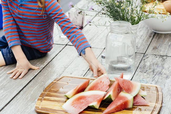 Midsection of boy reaching for watermelon slice at picnic