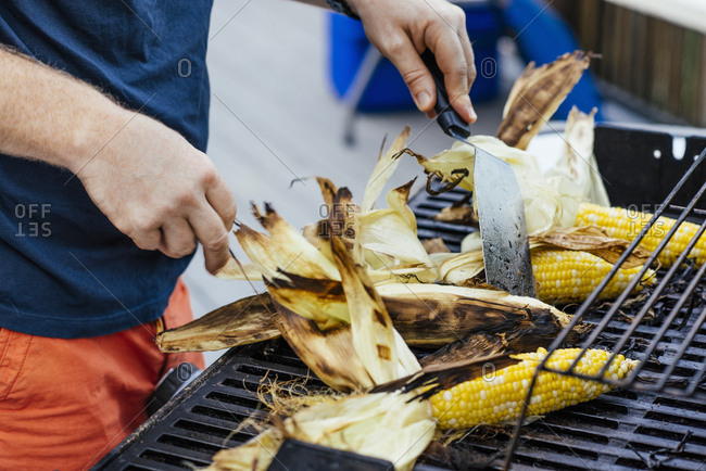 Midsection of man grilling corn on barbecue