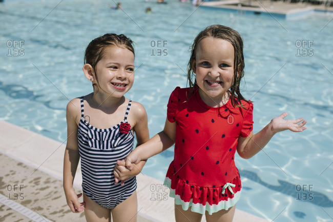 Two girls holding hands standing in front of swimming pool