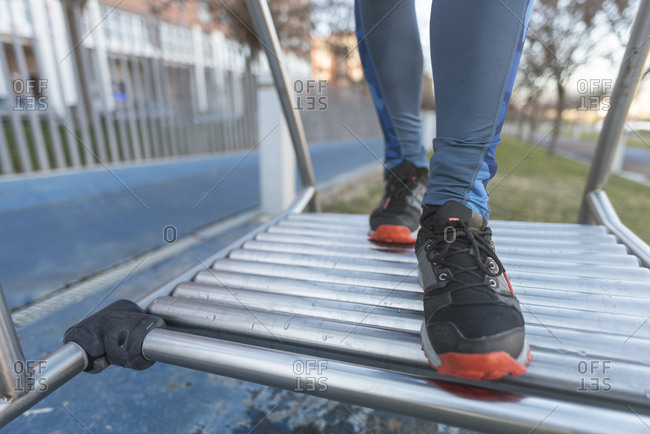 Closeup of sports shoes while training on outdoor exercise machinery