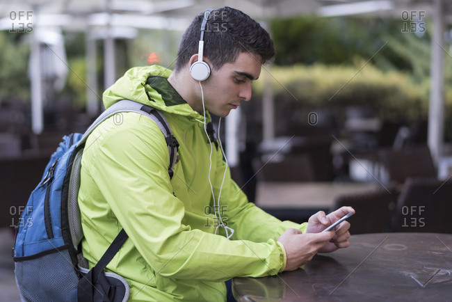 Young man listening to headphones while waiting at restaurant