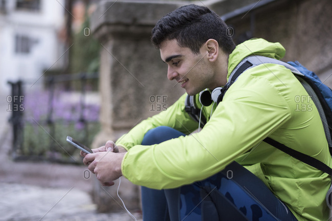 Young man texting on smartphone waiting outside smiling