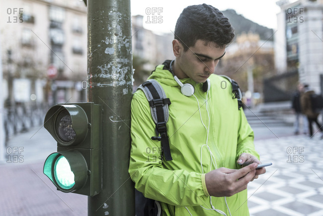 Young man texting on his smartphone while leaning on a traffic light pole