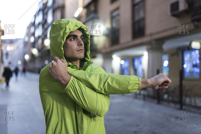 Runner with raincoat stretching after training