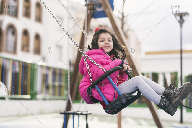 Young girl having fun swinging