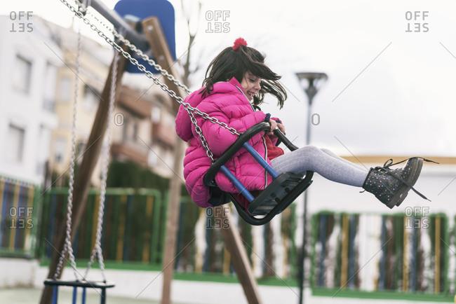 Preschooler having fun swinging at the park