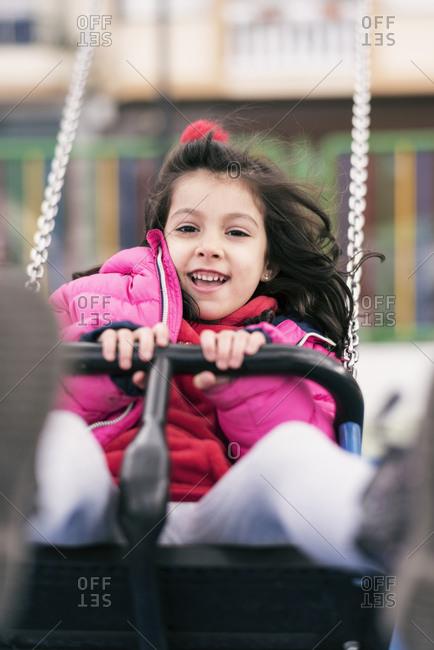 Little girl in mid-swing on swingset