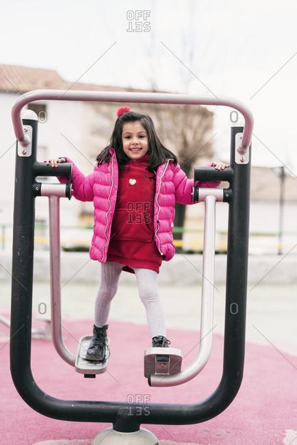 Small girl standing on playground equipment