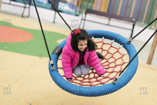 Young girl balancing on rope tire swing