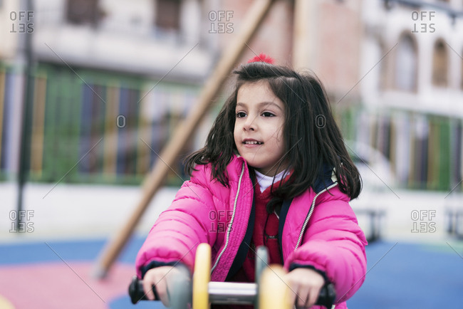 Little girl sitting on playground toy