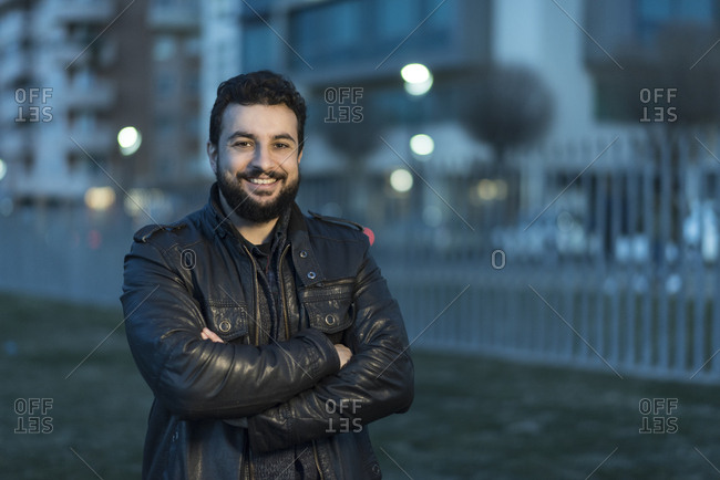 Arabic man smiling at camera at sundown in the city