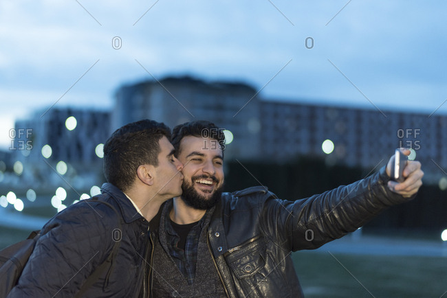 Happy couple posing for romantic selfie at dusk