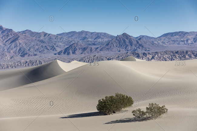 Sand dunes lay out in front of distant mountains in Death Valley National Park in Eastern California