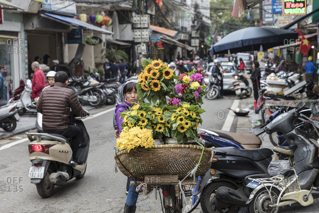 Hanoi, Vietnam - May 19, 2015: Vendor selling flowers on a bicycle on a busy street in the Old Town quarter of Hanoi