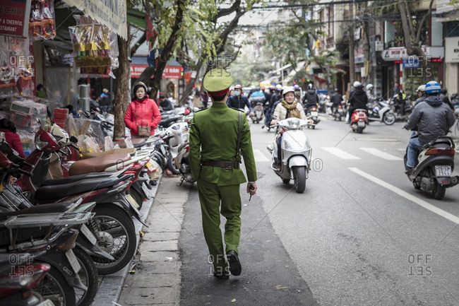 Hanoi, Vietnam - May 19, 2015: Military officer walking through crowded and busy streets