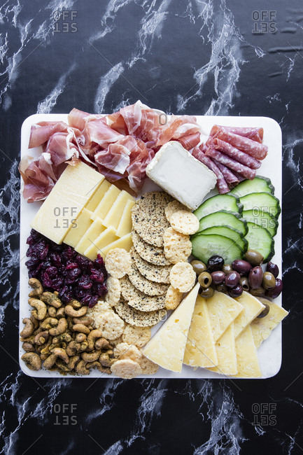 Square tray with vegetables, cheese, nuts, and deli meats on marble counter
