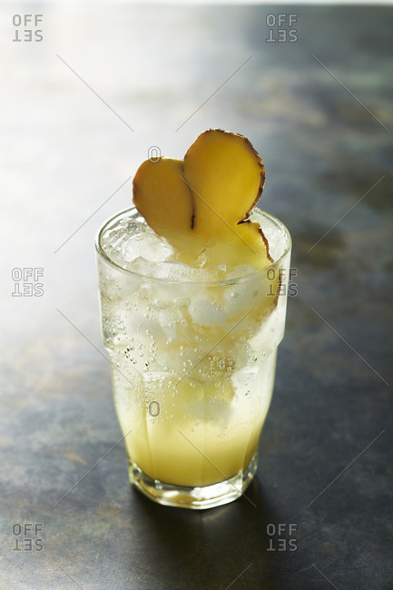 Glass of sparkling lemon ginger soda with ginger garnish