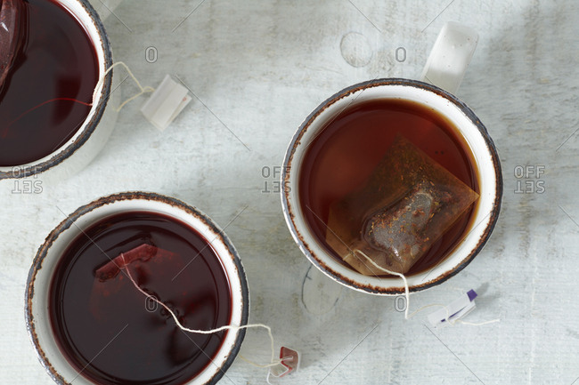 Cups of herbal tea on white rustic table