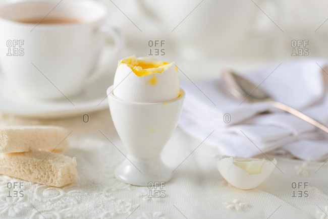 Cracked soft boiled egg in egg cup