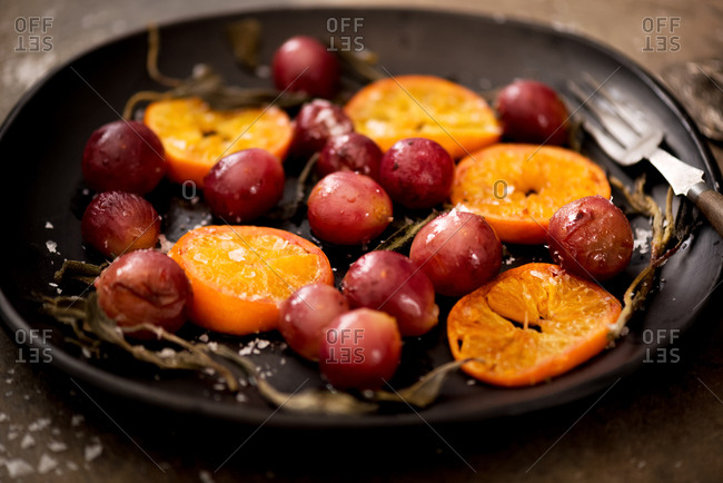 Roasted grapes and clementine oranges with sage in rustic subdued light setting