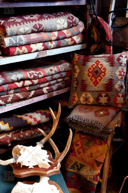 Woven rugs on a shelf beside animal skull and antlers