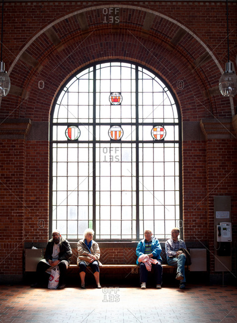 Copenhagen, Denmark - May 1, 2008: Seniors sitting on bench in front of larch arched window
