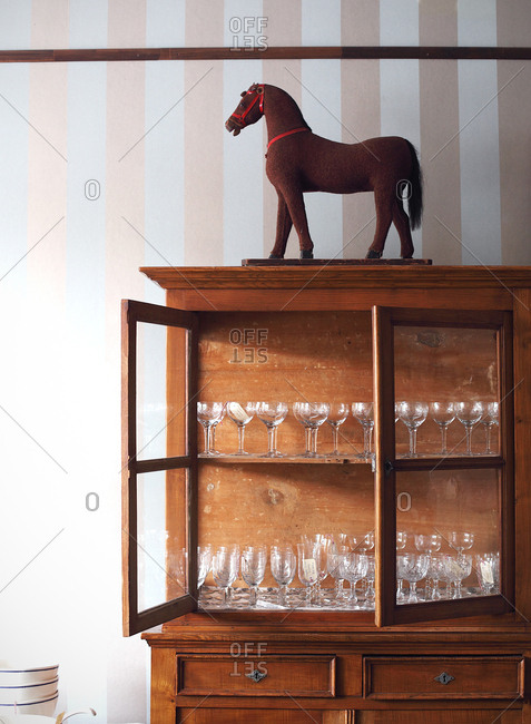 Assortment of glasses in a wooden hutch