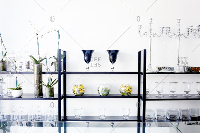 Glasses, plants and candleholders on a shelf