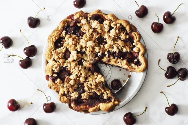 Overhead view of cherry crumb pie surrounded by ripe cherries