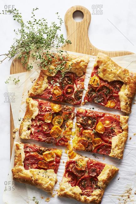 Overhead view of sliced Rustic Cherry Tomato Tart Provencal with lemon thyme garnish