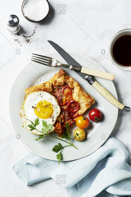 Overhead view of brunch of Rustic Cherry Tomato Tart Provencal served with a fried egg