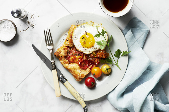 Overhead view of Rustic Cherry Tomato Tart Provencal served with a fried egg