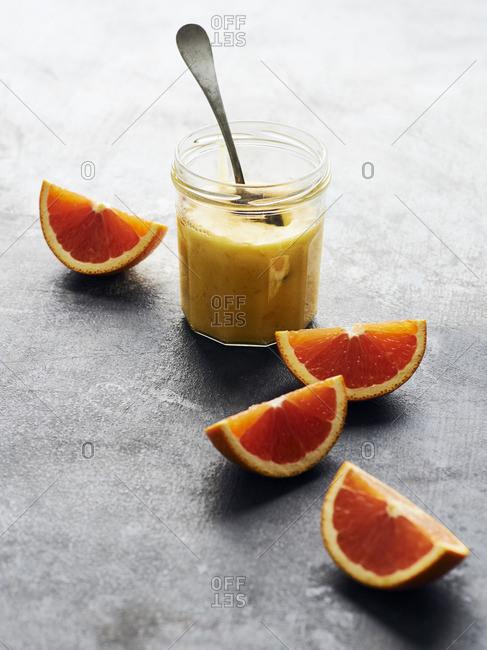 Jar of homemade orange curd arranged with slices of blood orange