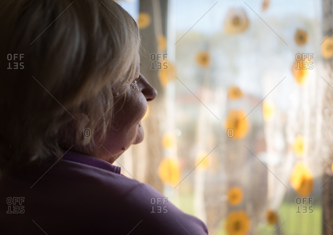 Solitary senior woman in front of window