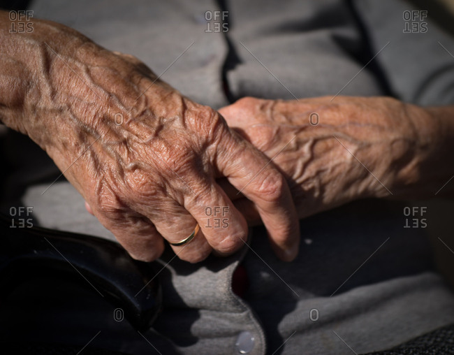 Hands of senior woman sitting in the yard
