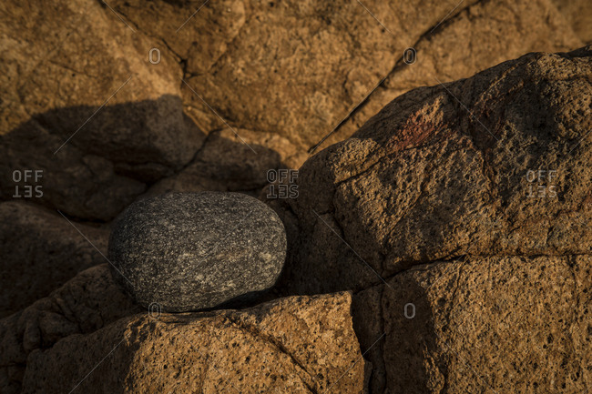 Rounded rock sitting on rock shelf highlighted by setting sun