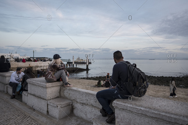 Lisbon, Portugal - 10 December 2016: People watching the world go by at Terreiro do Paco overlooking the ocean and the River Tagus
