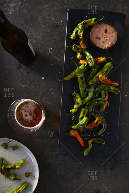 Grilled shishito peppers on a plate