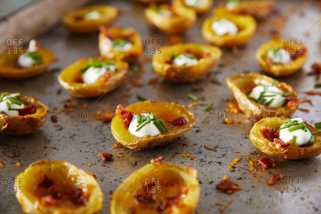 Loaded potato skins on baking sheet with sour cream, bacon and chives
