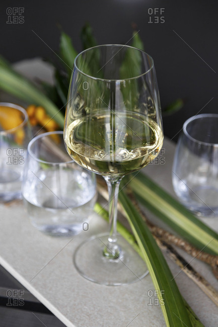 High angle view of glass of white wine and glasses of water arranged on bar