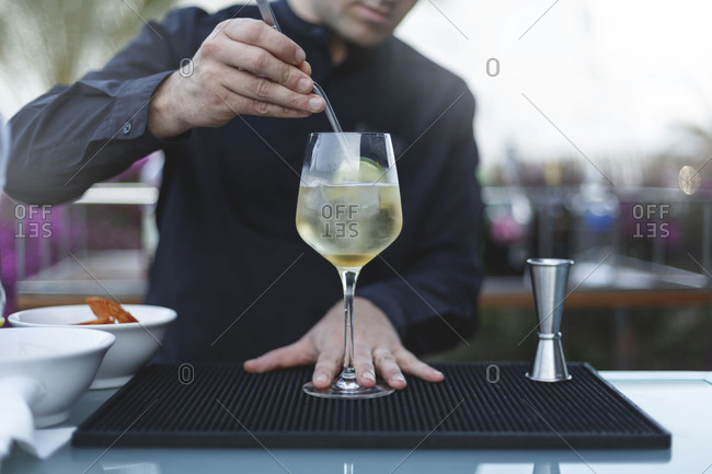 Close up view of barman preparing white wine cocktail