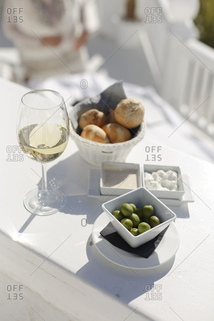 High angle view of glass of white wine served with  olives and bread rolls
