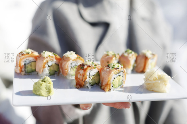 Waiter presenting salmon avocado sushi rolls arranged on plate