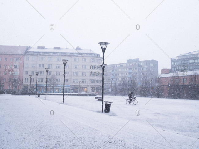 Woman cycling across square in the snow
