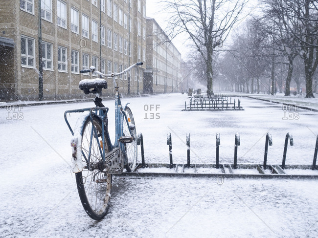 Single bicycle left in rack in the snow
