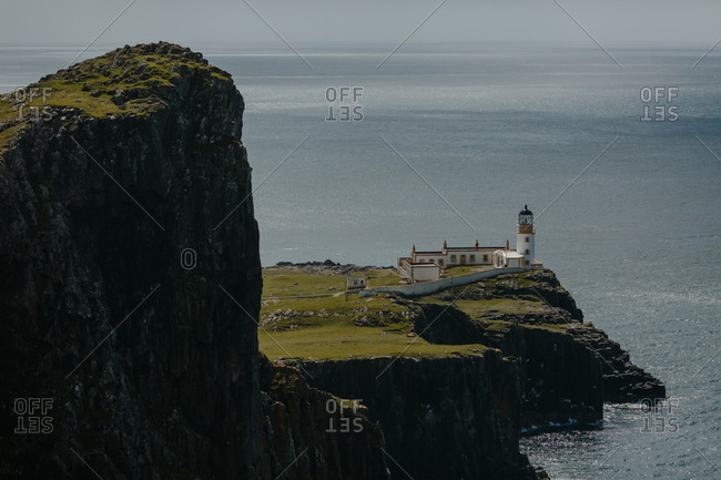 Lighthouse on mossy Scottish rock formation