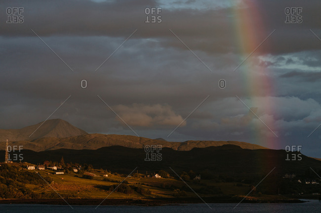 Vertical rainbow on shadowy shoreline at sunset