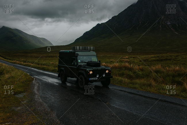Scotland - February 1, 2018: Vehicle driving on rural mountainside road in stormy weather