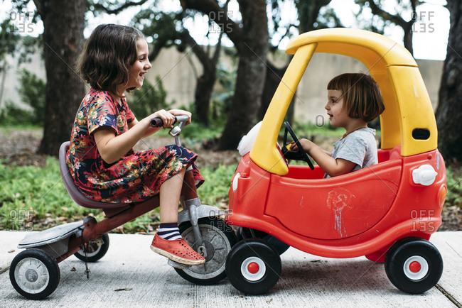 Sisters playing together outside ride toy car and tricycle